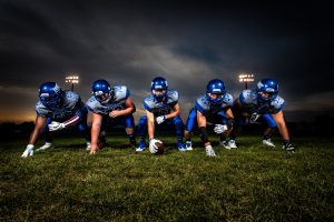football players in blue jersey lined under grey white 186076